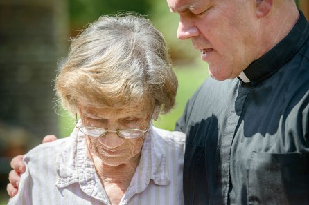 Trinity Lutheran Church Pastor Rev. David Buss prays with Trinity charter member Althea Neptune outside her flood-damaged home.