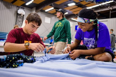 Students tie a fleece blanket by hand during a May 10 workday at Martin Luther High School.