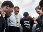The Rev. Dr. Roosevelt Gray, director of LCMS Black Ministry (with tie), and the Rev. Dr. Steve Schave, director of LCMS Urban & Inner-City Mission (second from right), pray with others along West Florissant Avenue on Aug. 18, 2014, in Ferguson, Mo. The LCMS recently unveiled a new webpage devoted to the subject of racism. (LCMS/Erik M. Lunsford)