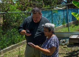 LCMS missionary to Puerto Rico Rev. Matt Ruesch assists Doris Rosado in communicating via satellite phone with her daughter, who lives in the U.S. Rosado and her family are members of Ruesch's parish, Iglesia Luterana Principe de Paz (Prince of Peace Lutheran Church), in Mayagüez, Puerto Rico. Hurricane Maria, which made landfall on Sept. 20, wiped out much of the island's power and communications grid. (LCMS/Al Dowbnia)