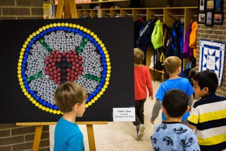Students at St. John's Lutheran School on Wednesday, Nov. 15, 2017, pass a decorative Luther seal made from plastic bottle caps in Racine, Wis. (LCMS/Erik M. Lunsford)