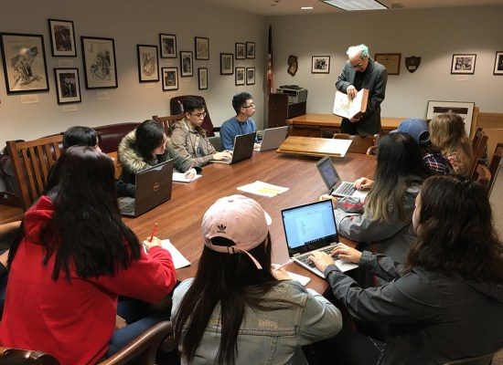 students viewing a book from Special Collections