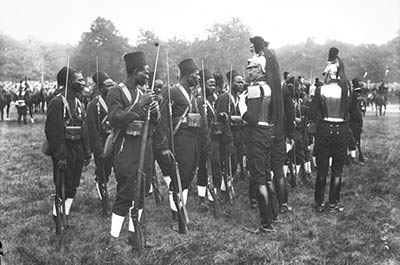 Senegalese Tirailleurs are addressed by an armored French Cuirassier at a1913 Bastille Day parade.