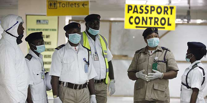 Nigeria health officials wait to screen passengers at the airport in Lagos.