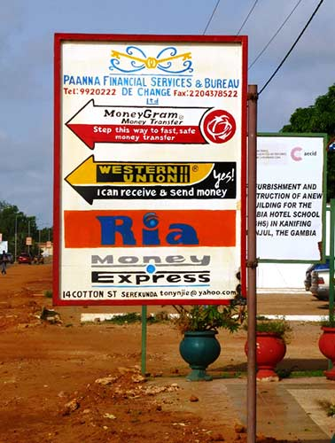 Many routes for remittances.  Handpainted signboard of international services offered by a local Gambian financial operator © Sylvia Chant