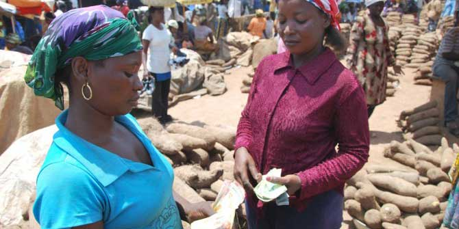 Two women conducting a business transaction in the market