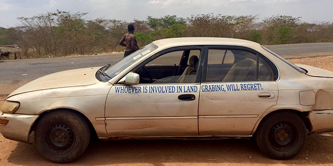A car with a slogan, Whoever is involved in landgrabbing will regret