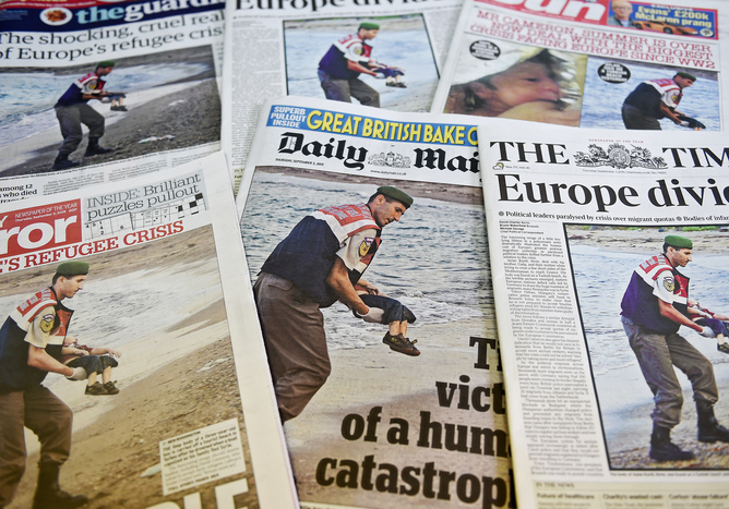 epa04910430 A picture of Turkish gendarmerie carrying the body of a child at the beach of Bodrum, Turkey dominates the front pages of British newspapers in London, Britain, 03 September 2015. Photos of the body of the three-year-old Kurdish boy from northern Syria who washed up on the shores of the Turkish resort town of Bodrum after an accident while his family tried to flee to Europe, has sparked shock and outrage. EPA/ANDY RAIN