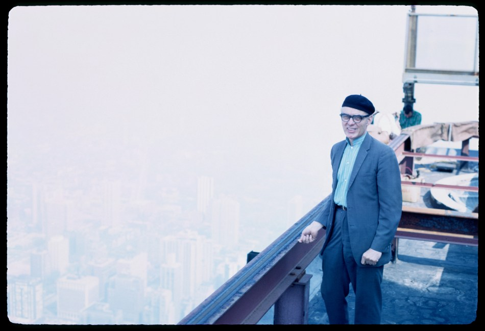 A smiling man wearing a beret standing beside a railing, with the city of Chicago far below .