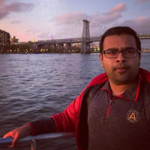 Maruf poses confidently for a picture in featuring a lovely bridge crossing a river in a sunset scene