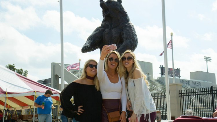 students taking a selfie with bear statue