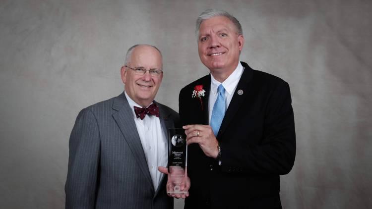 Randall Eggert holds his award with President Smart