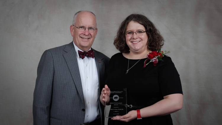 Dr. Krause holding award with President Smart