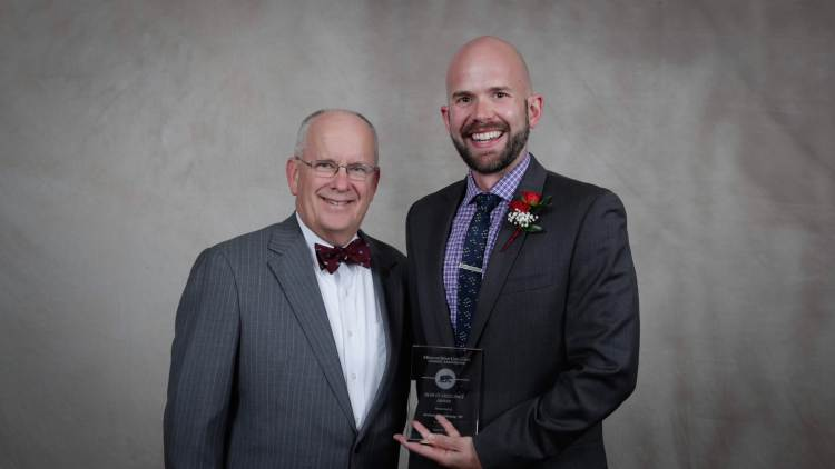 Andrew Shaughnessy holding his award with President Smart