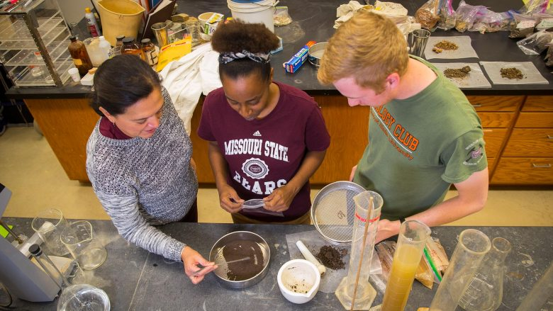 Melida Gutierrez working with students in the lab