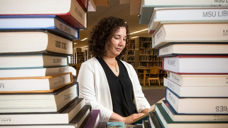 Dr. Linda Moser reading and framed by books
