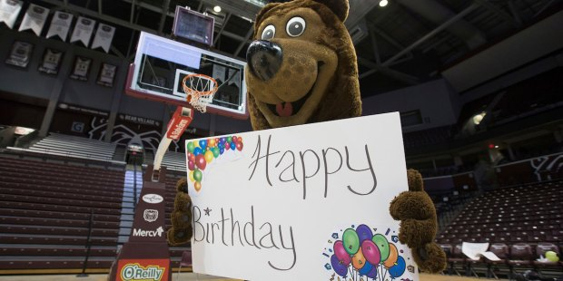Boomer holds birthday sign on basketball court