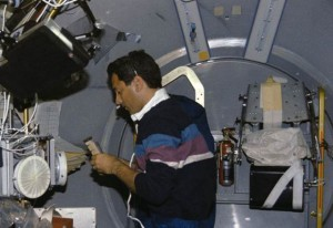 Astronaut Larry DeLucas, payload specialist, handles a Protein Crystal Growth (PCG) sample at the multipurpose glovebox aboard the Earth-orbiting space shuttle Columbia. (NASA)