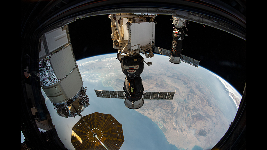 Three spaceships are pictured attached to the space station as the orbital complex flew 261 miles above the Bay of Bengal.