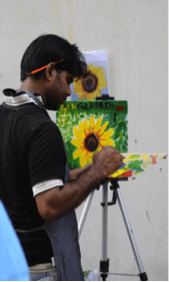 Migrant workers painting at Backalley Arts booth.