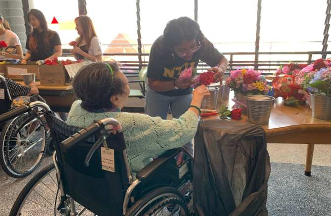 Helping a resident with her flower arrangement.
