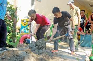 Mixing cement to build the aquaponics walls.