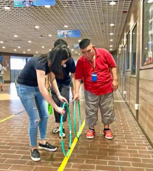 Volunteer demostrating on how to roll a hula hoop.