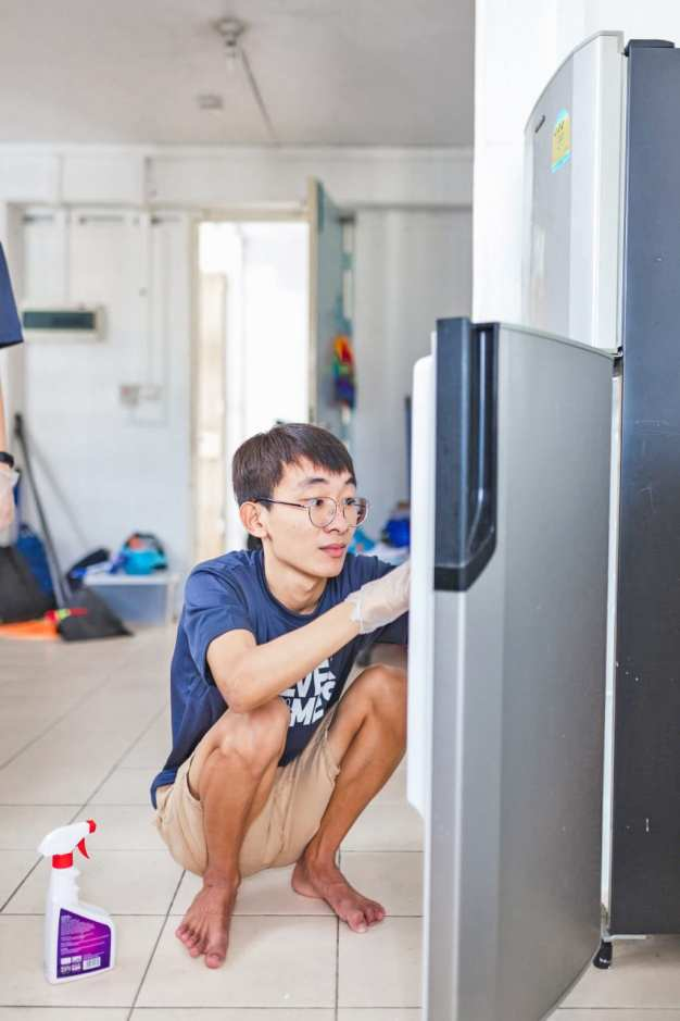Participant helping the elderly to clean her fridge.