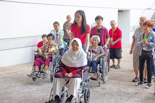 Volunteers helping wheelchair-bound participants to get into Nanyang Auditorium.