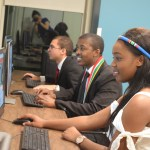 Nkululeko, Juliet, and Daniel sitting at computers.