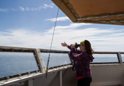 Alexa on-effort using binoculars to estimate the distance and bearing of a marine mammal sighted off the starboard bow. Image source: Alexa K.