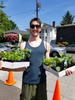 Smiling Incredible Edibles Plant Sale customer holding two cardboard trays filled with vegetable plant starts.