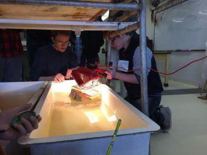 Students use a light to power their solar boat