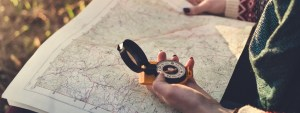 Compass On Background Of Map In The Forest