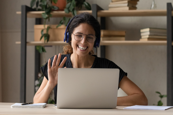 Smiling Woman In Headphones Greeting Talking On Video Call