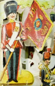 Regimental flag-bearing mustachioed guardsman, replete with monocle.