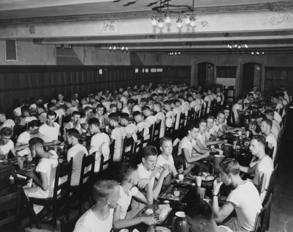 Navy officers in training wearing white t-shirts seated at long rectangular tables eating.