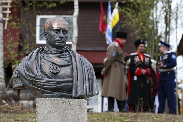 Cossacks stand behind a bust of Russian President Vladimir Putin which depicts him as a Roman emperor, during its unveiling ceremony in Leningrad region, Russia, May 16, 2015. REUTERS/Maxim Zmeyev