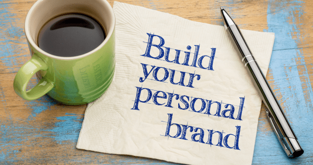 Mug, pen, post it with build your personal brand written on it.
