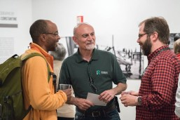resident Ali Malekzadeh (center) mingles at exhibit reception.