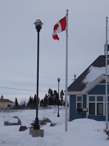 Maple Leaf Flag outside new RCMP (police) building in Innu village of Sheshatshiu. The Innu word on the RCMP sign means  `The house of the people who grab you.`  Photo Anthony Jenkinson.