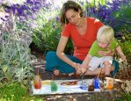 Leah Mebane painting with natural earth paints she created herslef, with her son Django