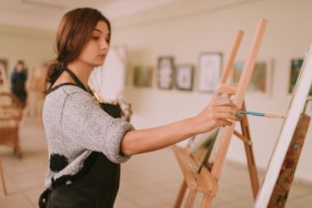 image of a young woman painting at an easel