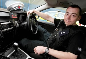 Adam Greenslade sitting in his police car