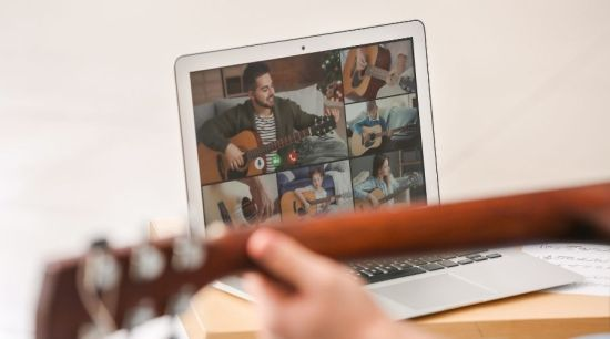 people playing the guitar together during a Zoom call