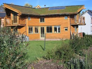 John Willoner's Eco-House at Findhorn. Turf roof, passive solar, solar panel. This image is public domain.