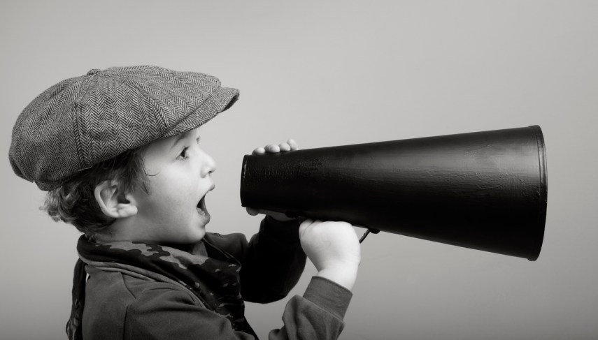 Little boy with newsboy cap shouting on old fashioned megaphone.