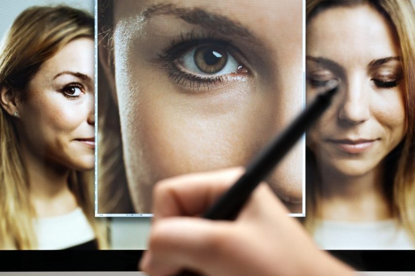 Image of a hand with professional digital tablet retouching and cropping multiple digital photographs of a woman. Sharp focus on screen.