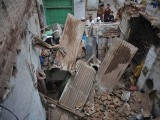 Residents look at a damaged house following an earthquake in Peshawar. PHOTO: AFP