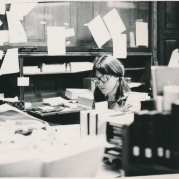Black-and-white photo of a woman sitting behind a desk